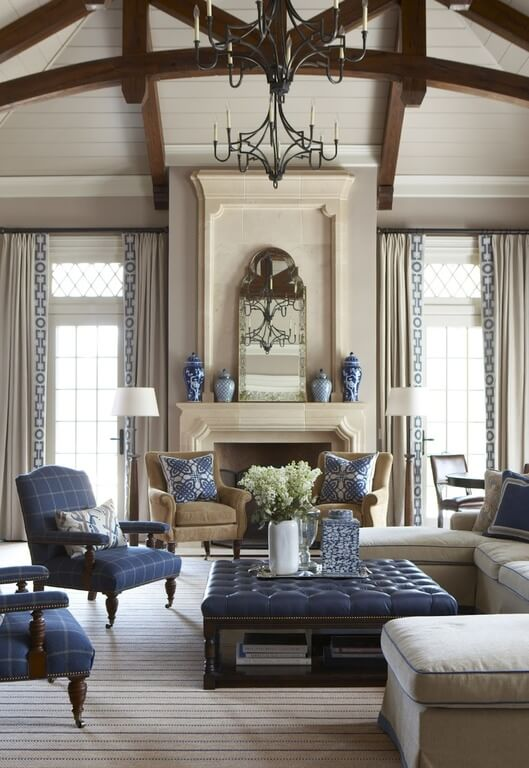 Stately living room features bold mixture of beige tones and navy blue. Ottoman coffee table, armchairs, pillows, and mantle-mounted vases all feature blue, standing out in an otherwise neutral setting.