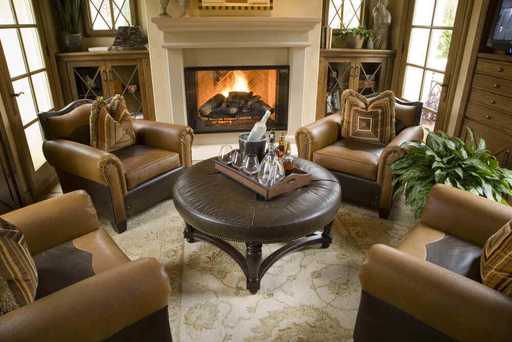 This Is An Elegant Sitting Room With Large Comfy Armchairs Around A Circular Ottoman Table