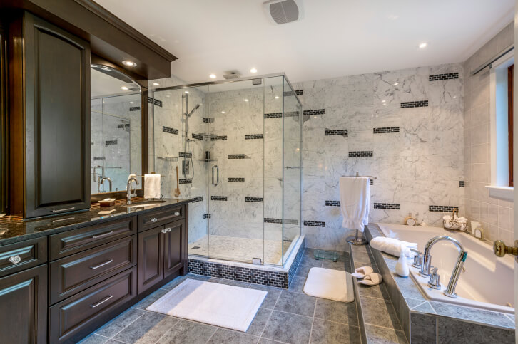 A plethora of textures and tones throughout this bathroom include grey floor tile and bath surround, marble wall detail sprinkled with patterned brick work, and lush, dark wood vanity reaching floor to ceiling.