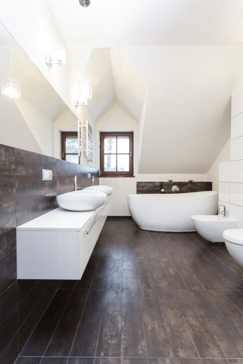 Arched ceiling bathroom in dark brown and white, featuring lengthy white double sink vanity and soaking tub paired against rustic look natural wood paneling.