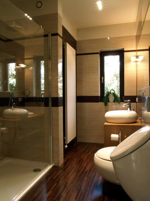 Bathroom holding a modern, minimalist touch, with natural wood vanity holding rounded vessel sink, dark hardwood flooring, and glass walk in shower.