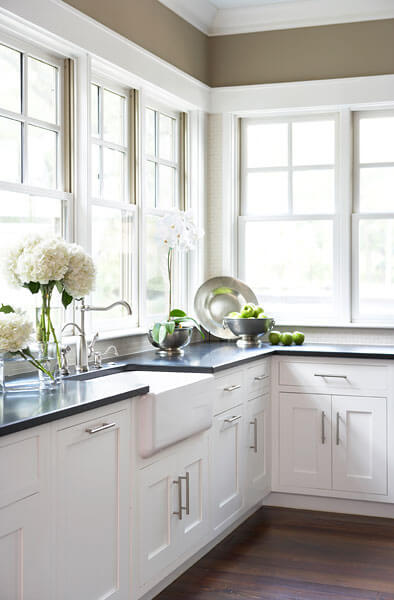White wood cabinetry and black countertops define the kitchen as much as the ubiquitous windows wrapping around, providing ample sunlight and views.