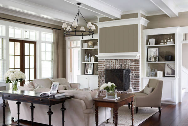 The living room surrounds its grey sofas with arrow-foot wooden tables, before a large brick fireplace flanked by built-in white wood shelving. Room by Linda McDougald Design and Photo by Rachael Boling.