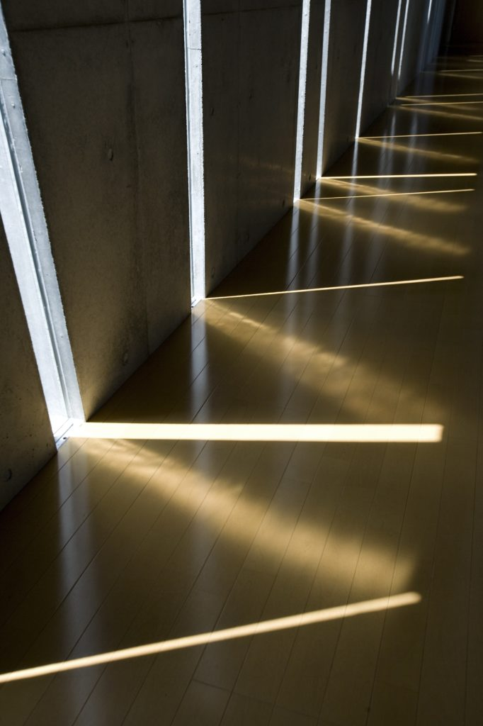 Close view of the natural hardwood flooring highlights the interplay of light from different angles. The sharp lines and soft glows work together to illuminate the home.