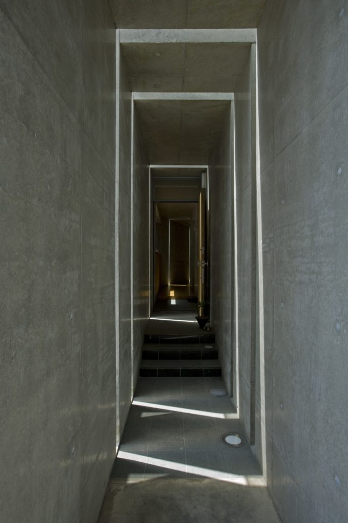 A different hallway as seen further from noon, with lines of light crawling up the interior wall. Concrete flooring meets grey tiles in this part of the home.