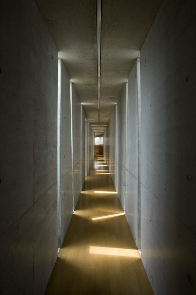 Notice the interplay of light from the opposing slits in the lengthy hallway. Throughout the entire space, sharp illumination comes directly from the sun-facing side, while a gentle glow comes from the opposite.