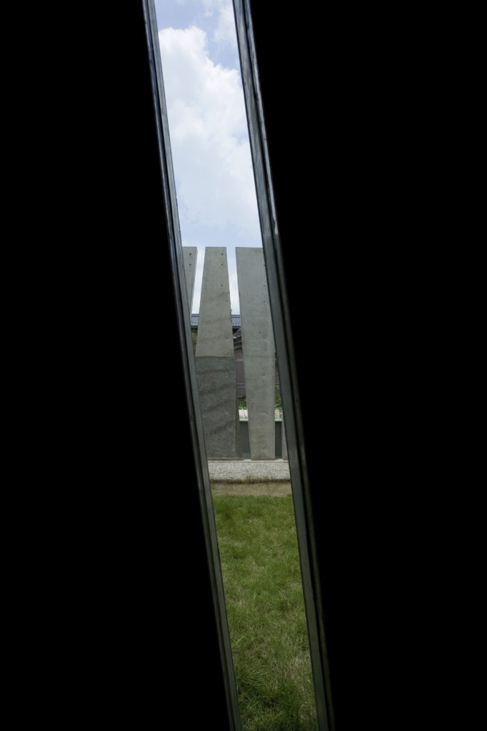 Looking through one of the diagonal slits, we see the lawn and exterior privacy wall.