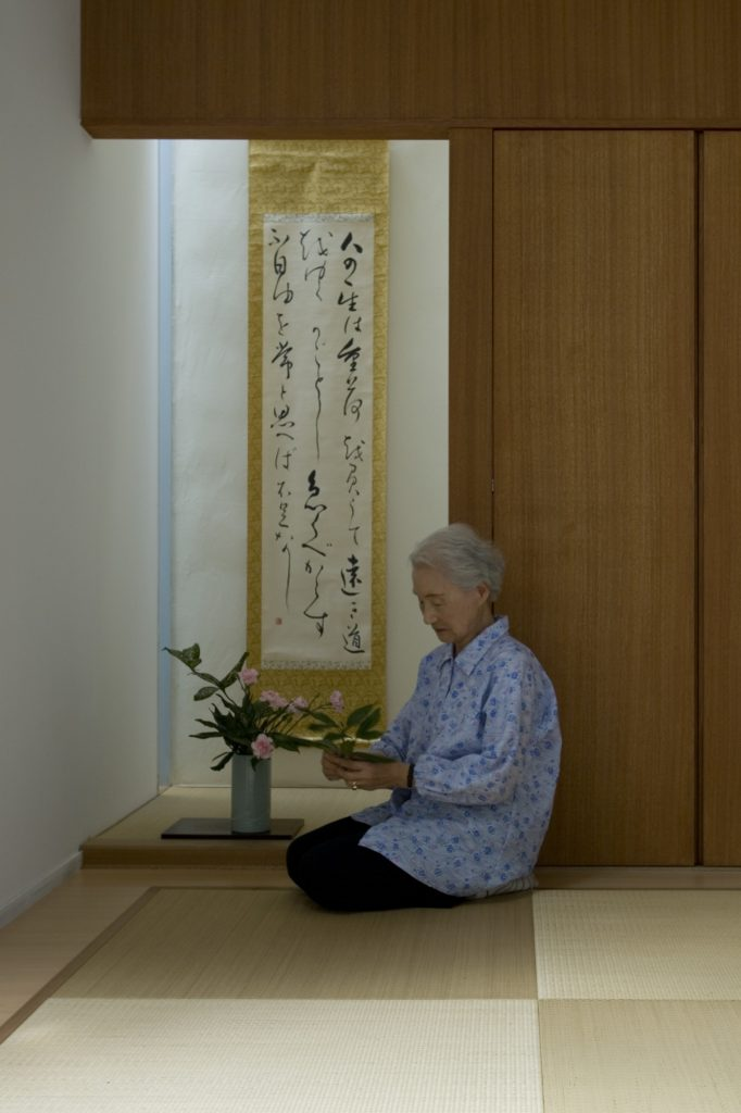 The homeowner is seen practicing ikebana, the art of flower arranging, in a private area of the home. Soft dark natural wood tones on the wall and ceiling stand over light hardwood flooring and more of the bamboo area mat.