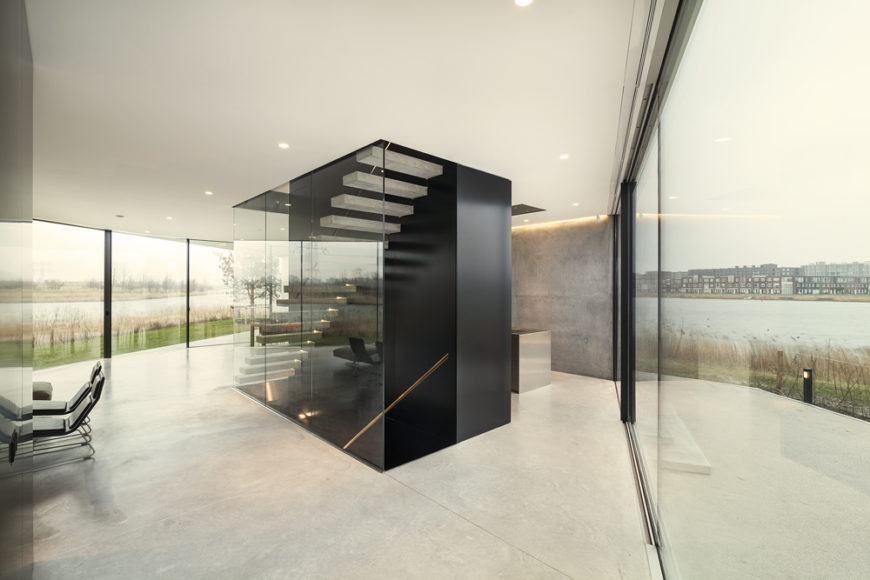 The central, structurally supporting stairway shaft stands out in black over a sea of white marble. Glass exterior provides views over the river from every angle.