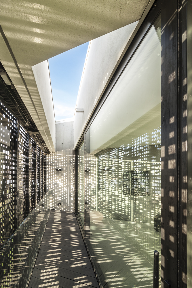 Gap between the exterior perforated shutters and glass wall showcases the intricately diffused natural lighting.