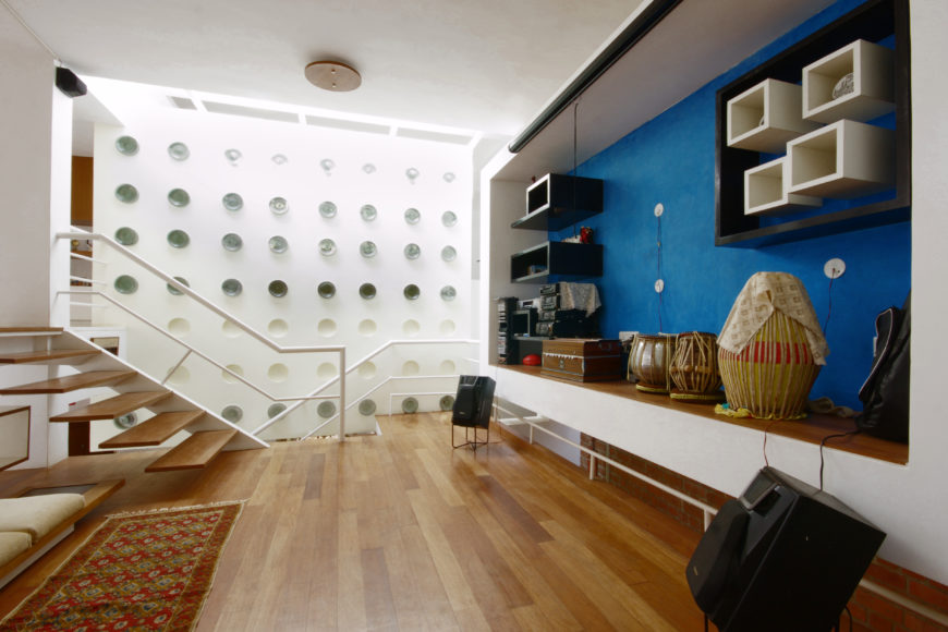 Central family room features unique blue-backed entertainment wall, with built-in cubic shelving and space for musical instruments. Transparent dotted white wall stands behind main staircase, comprised of floating wood steps.