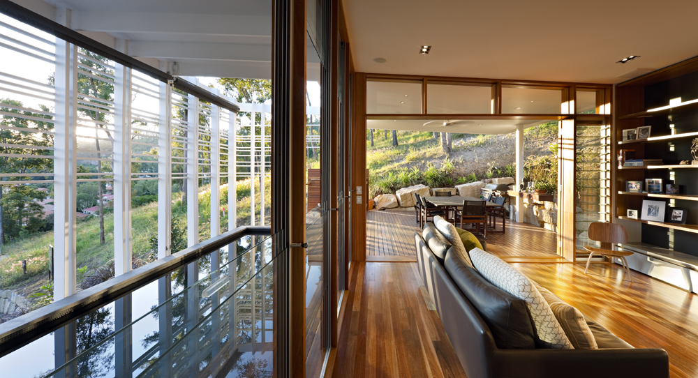 The living room is clad in rich natural wood, extending out onto furnished, sheltered patio space.