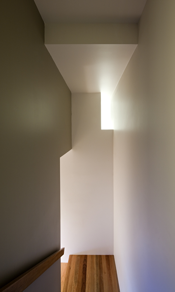 Main staircase continues expanse of white and natural wood contrast, with clever pockets of light filtering through.
