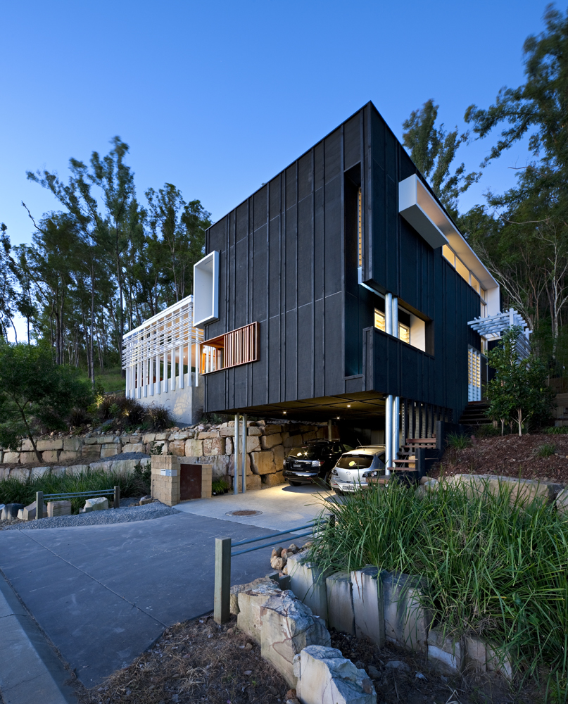 Angled view of the entire home highlights the main cubic structure, along with white and natural wood details cut into the structure, over sloped environment.