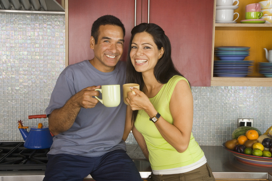 Couple drinking coffee in the kitchen.