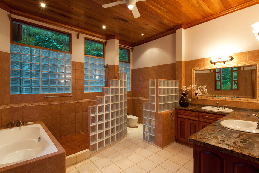 Intricate, lush bathroom stands artful brick cube walls between shower, toilet, and vanity spaces. Beneath a hardwood ceiling, dark wood cabinetry under dark marble countertops, light brown tiling, and white floors add variety of texture.