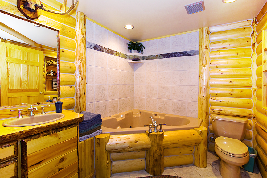 Bright tile flooring pairs with natural wood vanity and log-style walls in this cozy bathroom featuring large, corner style jacuzzi tub.