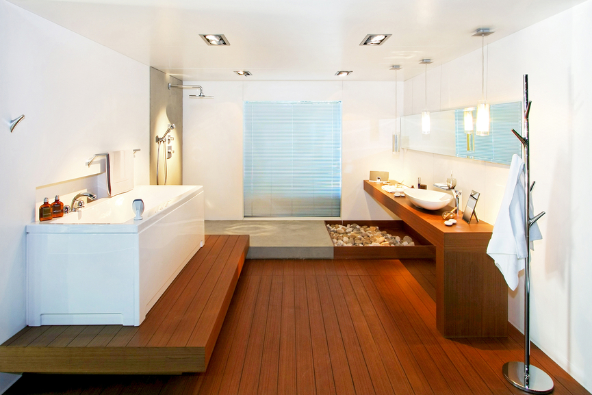 Striking Zen style informs this bathroom, with lush natural wood flooring and raised bath platform, with matching minimalist vanity, in all-white surroundings.