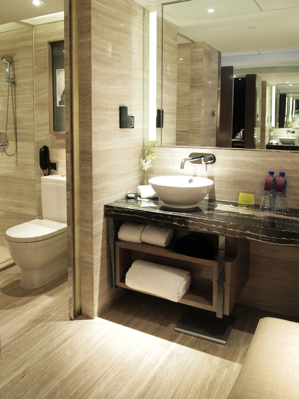 Grey marble bathroom features muted natural wood vanity storage beneath black marble countertop with white pedestal sink.