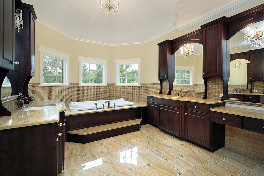 Similar shaped bathroom here, equipped with rich, dark wood cabinetry on twin vanities and bathtub frame, paired with warm beige marble flooring and half height micro-tile wall detail.