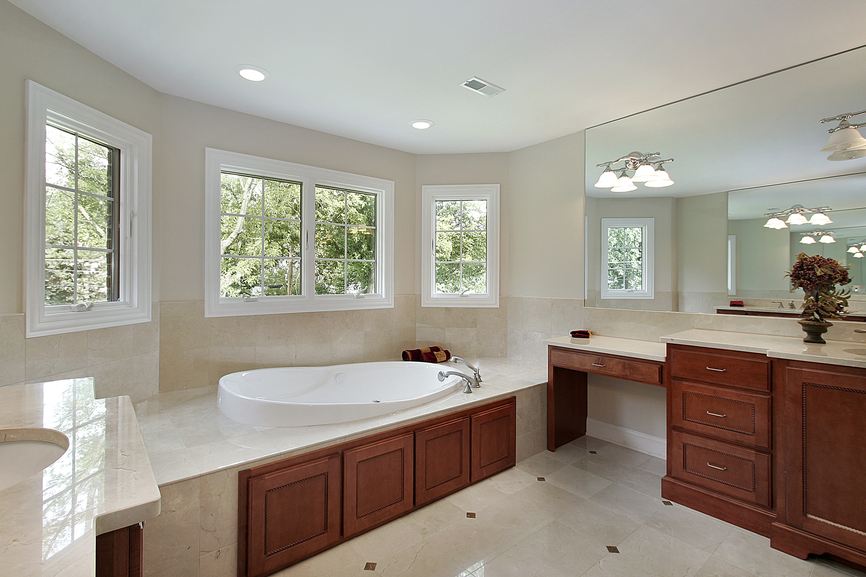 Here's another U-shaped bathroom, featuring high contrast between cherry wood vanity cabinetry and bathtub detail, and light marble flooring and walls.