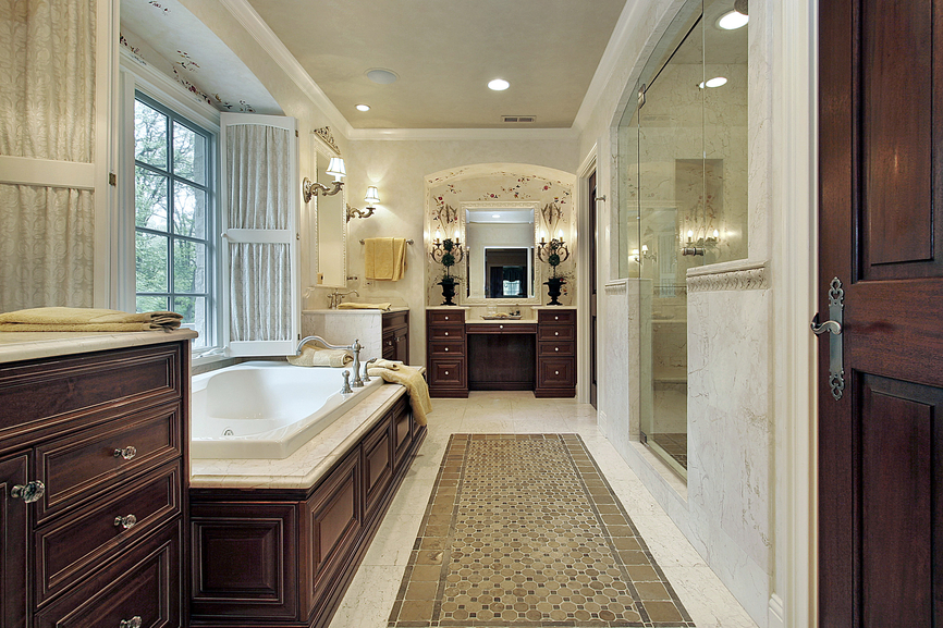 Lengthy bathroom stands rich dark cherry wood - from vanity to bathtub frame to cabinetry - over white marble flooring and countertops, with large walk in glass door shower on right.