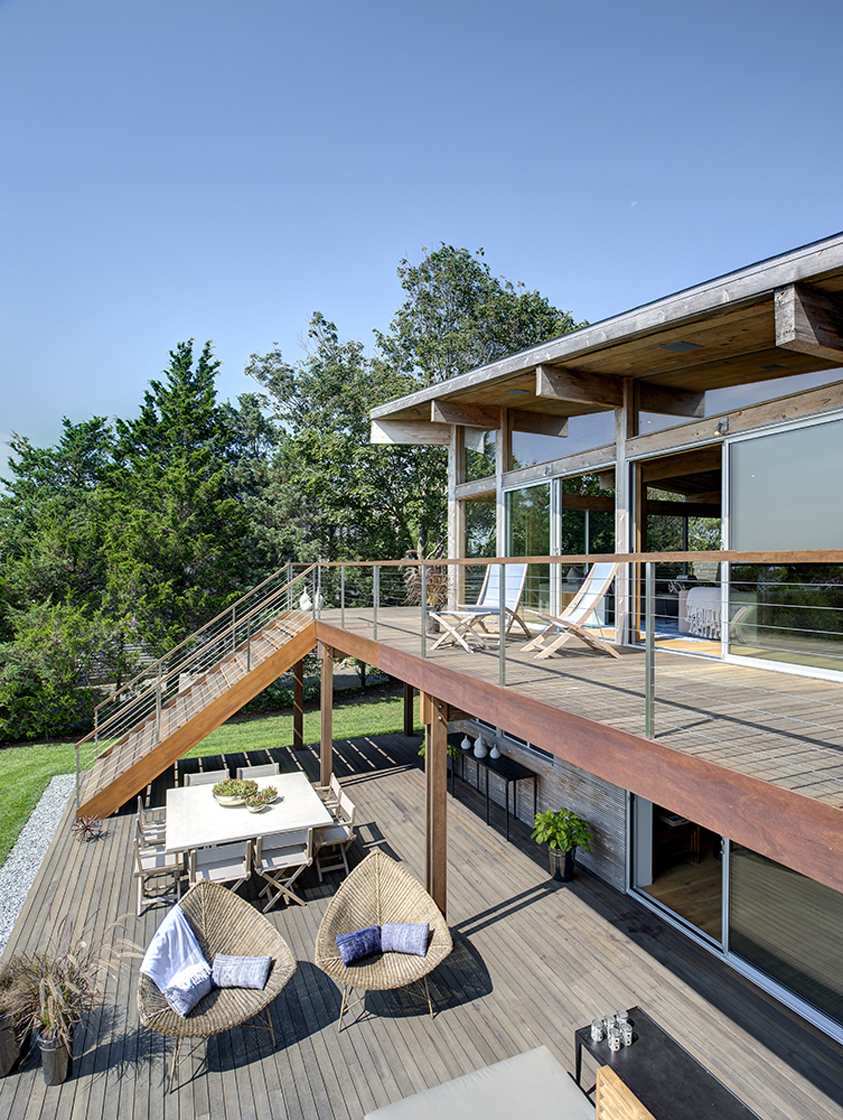 This angled view of the balcony highlights the natural wood flooring throughout both patio levels, the unique twin teardrop chairs below, and exposed beams over folding chairs above.