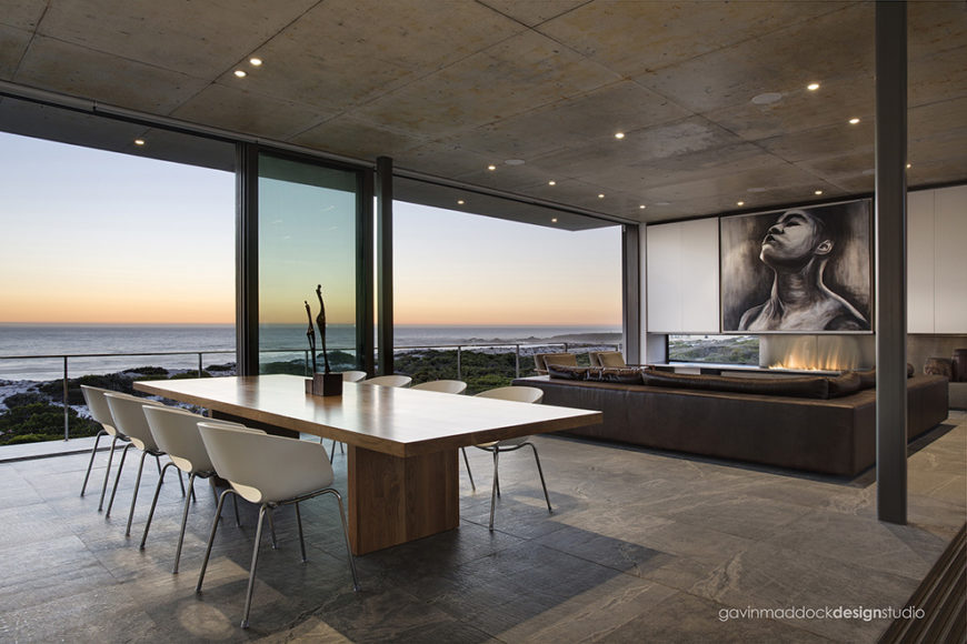 The central open space shares the living room with this large all wood, minimalist dining table. White plastic moulded and metal frame chairs add modern contrast over the concrete flooring.