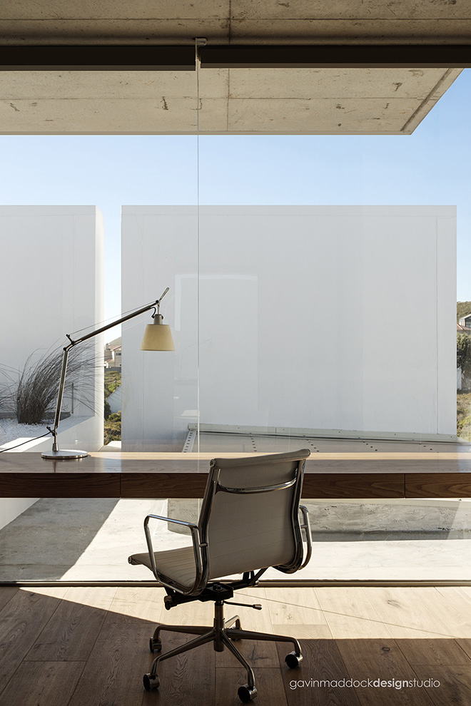 The home comes complete with full office space, including this hardwood desk mounted to the glass wall, with full views of patio and surrounding nature.