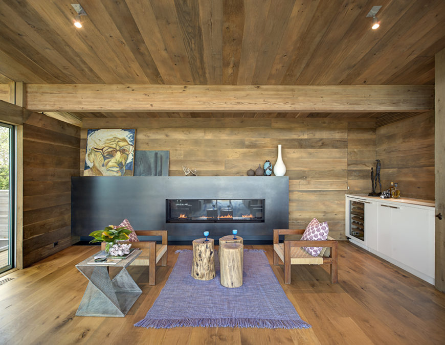 """This more intimate seating area utilizes three of the treated trunk pieces as a loosely defined """"coffee table"""" between twin cubic wood chairs. White counter and cupboard structure is built into right wall, contrasting with monolithic black fireplace surround at center."""