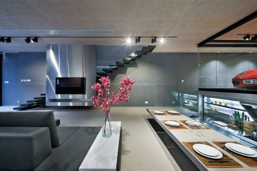 Perpendicular view reveals the lowered kitchen area and dining table set at floor level, while glass-shrouded staircase floats on opposite wall behind metallic media slab.