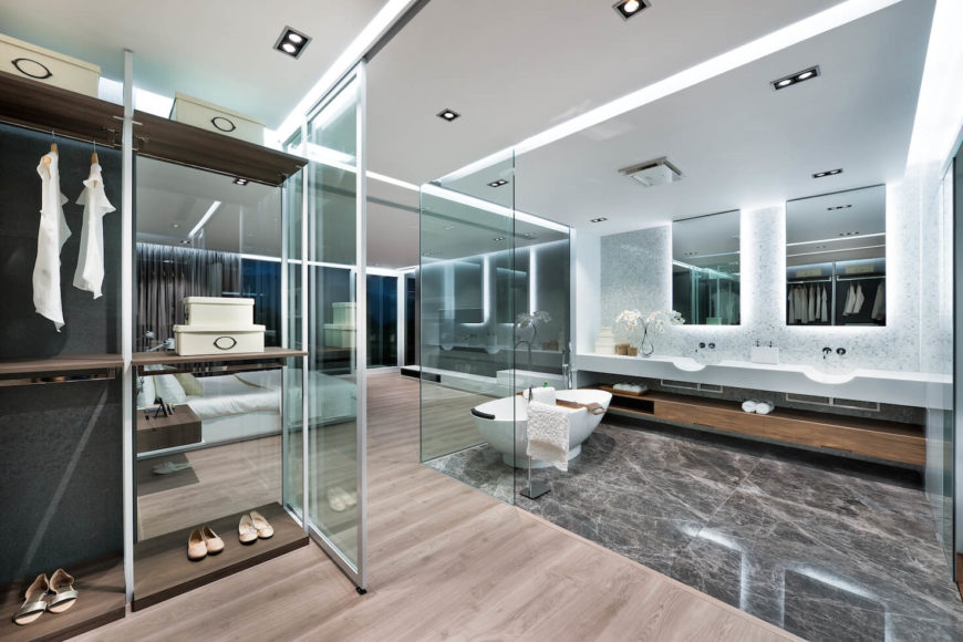 Top floor master bedroom suite is comprised of singular open space, divided by glass walls. Bedroom itself can be seen through closet and bathroom.