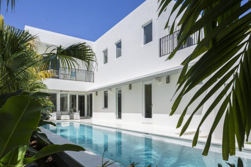 Lido pool runs the length of the rear facade, with white patio surrounding and tropical garden bordering outer edge.