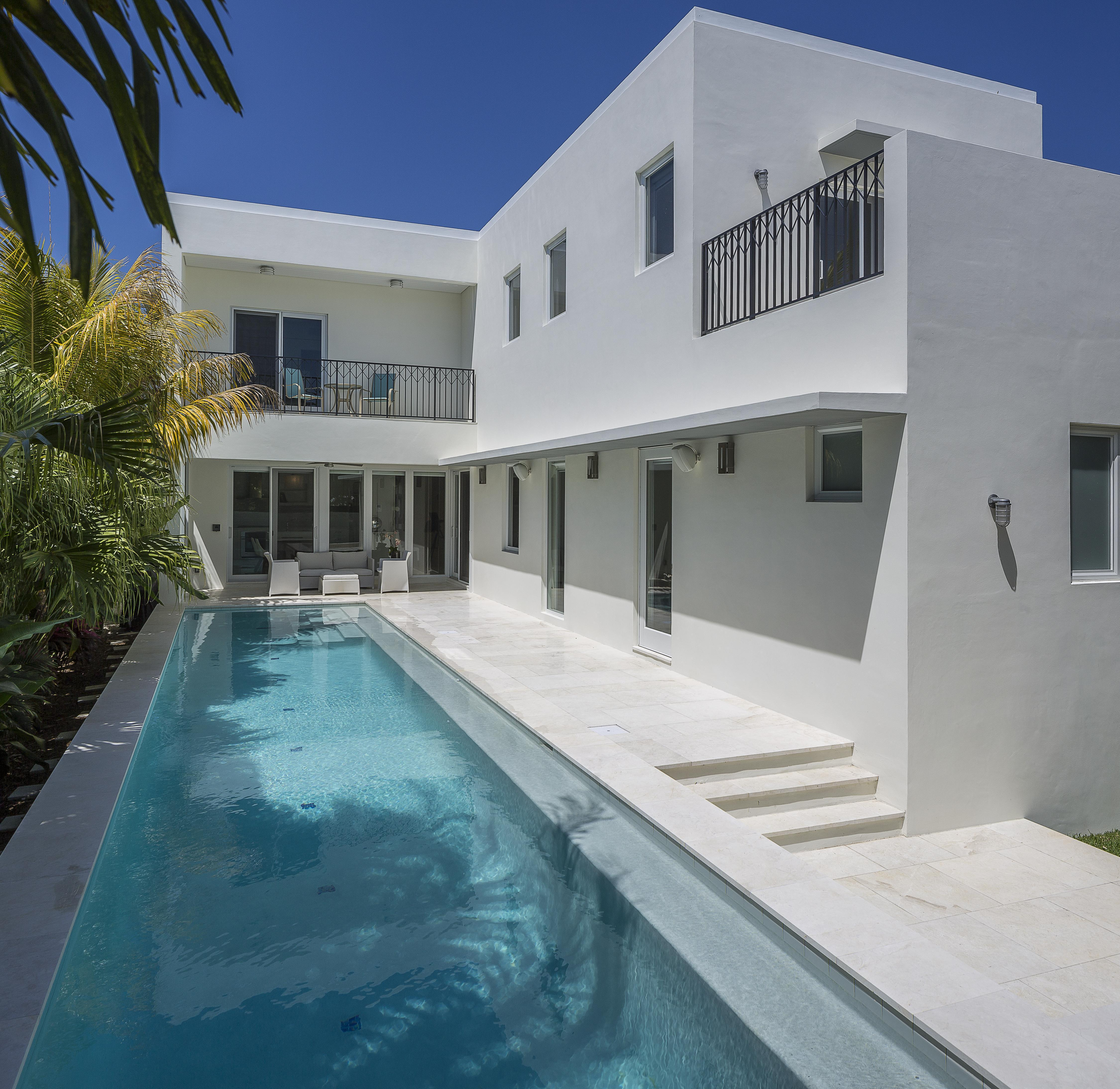 This raised view of the pool and patio highlights the extensive marble tiling and covered seating area below second floor balcony.