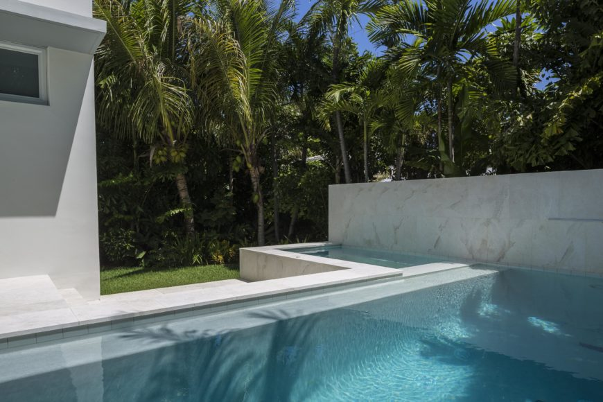 Pool is wrapped in marble tiling, forming exterior wall and attached jacuzzi border.
