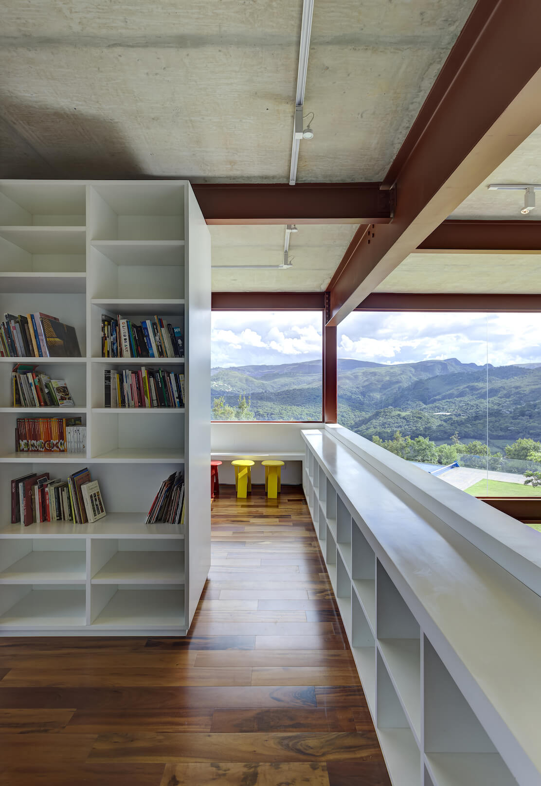 Inner edge of the library space, with more white wood shelving built into the dividing wall overlooking the open living room space at right. Color dots the neutral and natural tones via small wooden seats at far end.