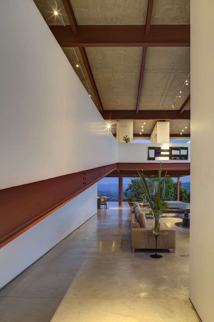 The large beams delineate sections of the home, and provide visual connection throughout the large open spaces. Above, we can see the lights suspended from the concrete ceiling.