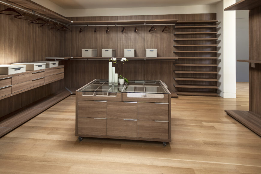 Immense walk-in closet space is awash with natural wood throughout, with shelving and drawers built into the walls, matching a caster-mounted, glass-topped island at center.