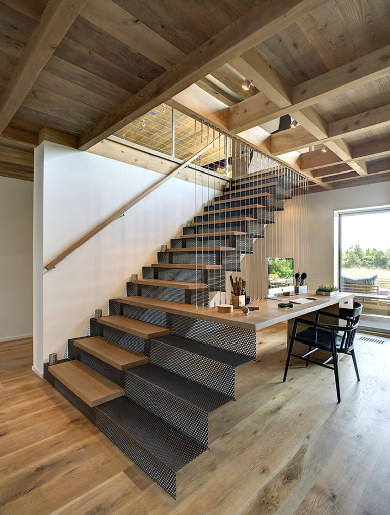 This lower level office space features unique natural wood desktop extending from stair structure, suspended via cables attached to central exposed beam.