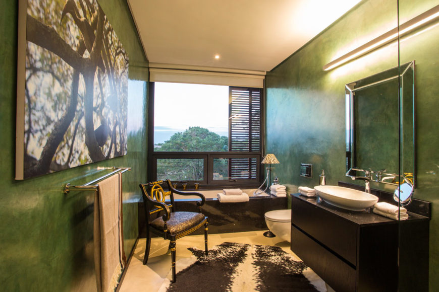 Bathroom offers fresh palette of forest green walls, with dark toned bathtub and vanity featuring vessel sink.
