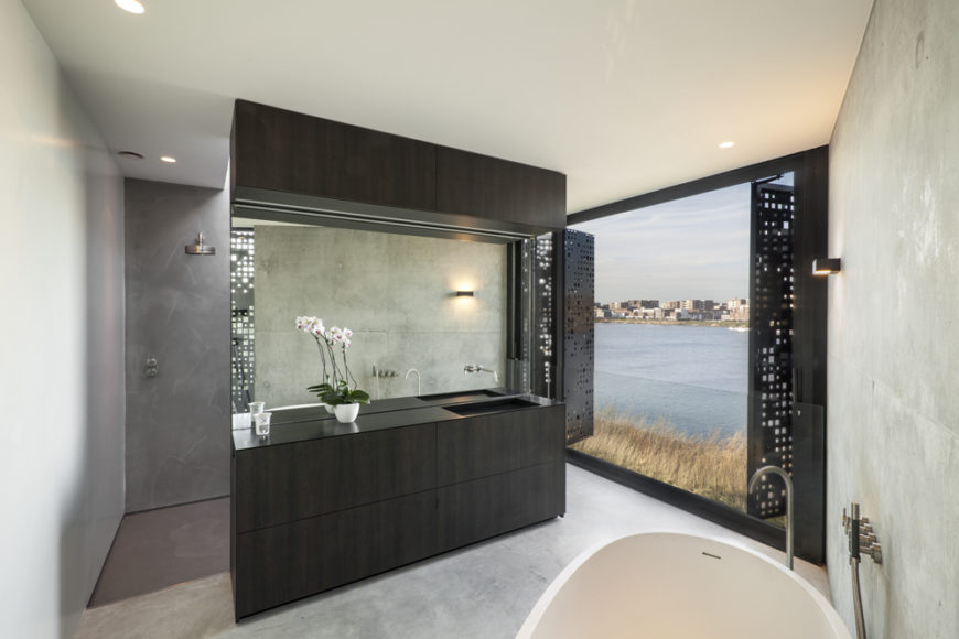 Bathroom on the upper floor stands behind another set of the perforated shutters, with dark wood vanity set between white pedestal tub and open shower space.