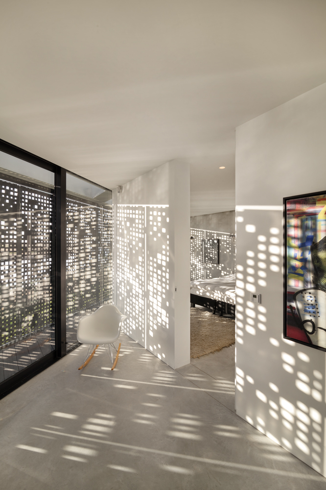 "The ""code"" patterned shutters provide moments of striking dappled sunlight throughout the home, as seen in this view of the upper hallway and bedroom."