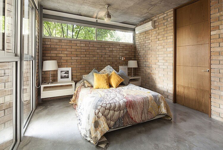Bedroom continues the warm brick walls and concrete flooring, lit via floor to ceiling windows at left. Pair of floating white shelves bookend the bed beneath a horizontal slit window.