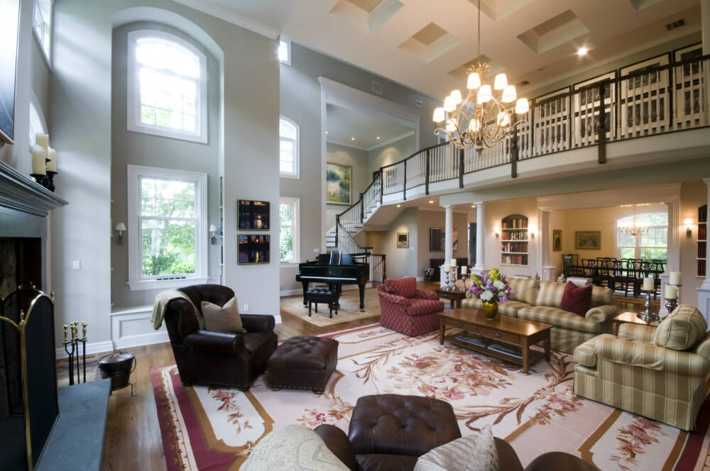 Massive Two Story Living Room Centered Around Red Floral Area Rug,  Featuring Dark Leather Chairs