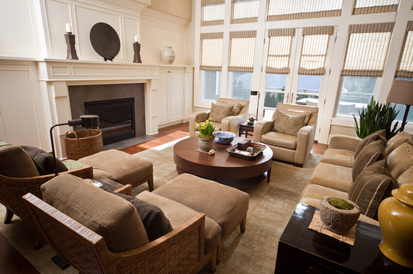 Complex variety of textures in this room include smooth wood coffee table, corduroy armchairs with wicker frames, leather armchairs, and cloth sofa, all standing beneath full height windows and a massive white fireplace surround.