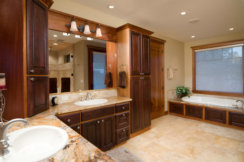 Another wide bathroom featuring immense dark natural wood vanity cabinetry, featuring swirled marble countertops and beige tile flooring, with matching wood trim on the bathtub surround, window frame, and door.