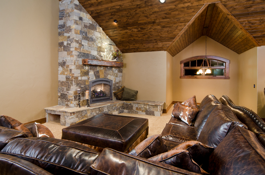 Rich, dark leather sectional dominates this living room, featuring a large corner stone fireplace and vaulted hardwood ceiling.