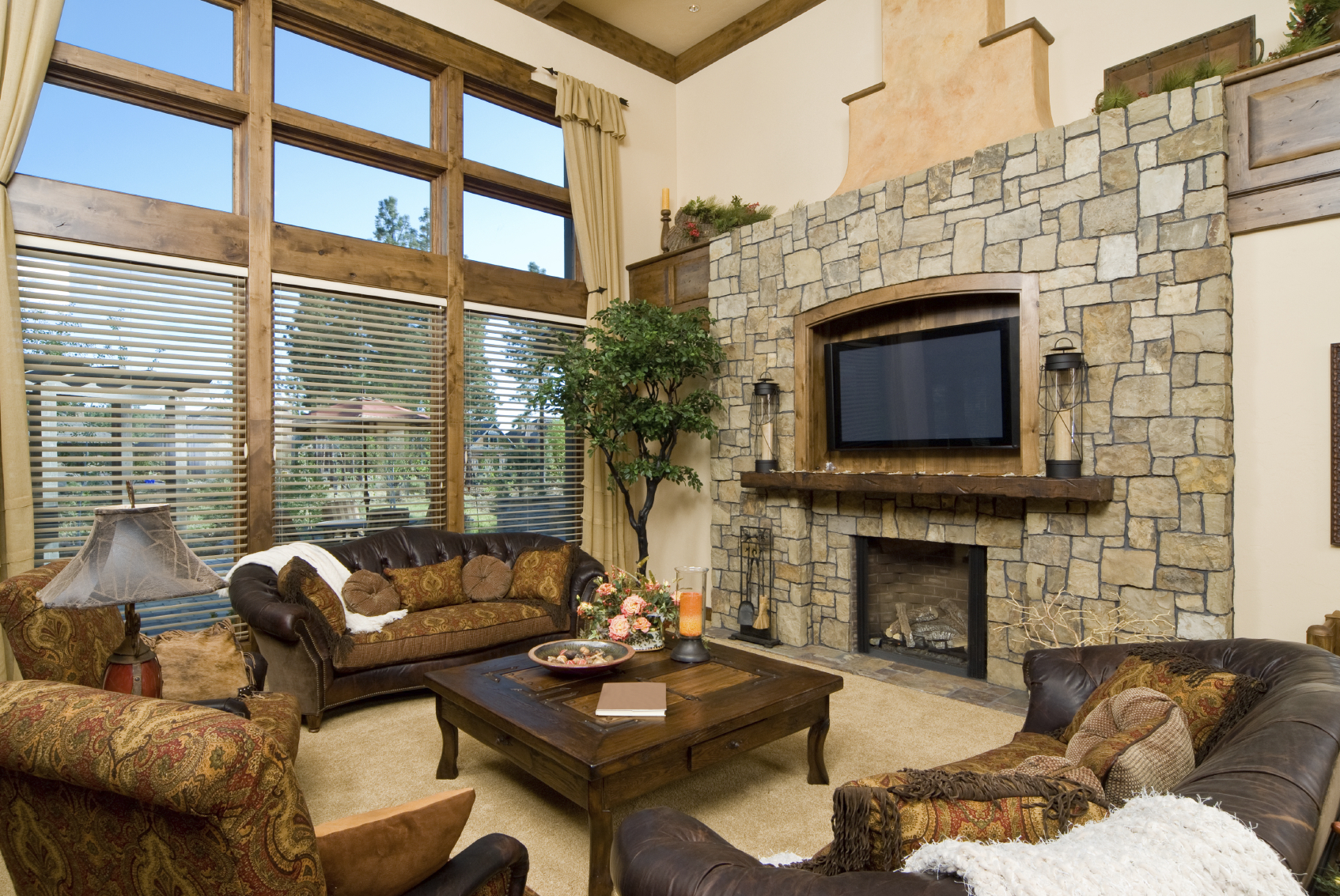 Here's another luxurious, rustic styled room. Wide stone fireplace surround includes wood mantle and TV mount, while camel back leather sofas and patterned armchairs circle a large carved wood coffee table. Natural wood frames full height windows.