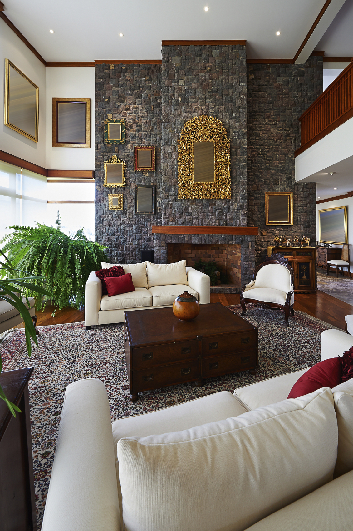 this luxurious room is dominated by massive stone fireplace wall looming over a rich hardwood