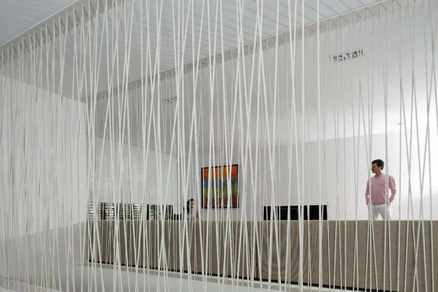 "Central living space is divided by a unique white wire transparent ""wall"" wrapped around central staircase."